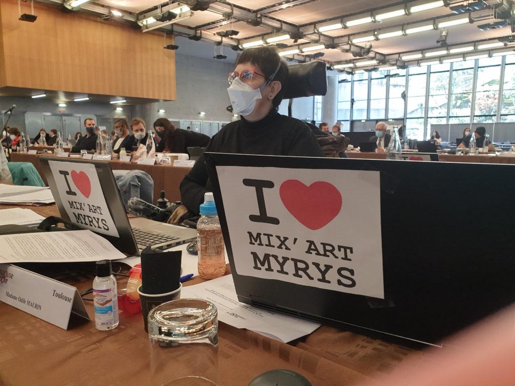 Photo d'Odile Maurin lors du conseil de Toulouse Métropole du 1er avril 21 avec un message de soutien à Mix'Art Myrys sur son ordi